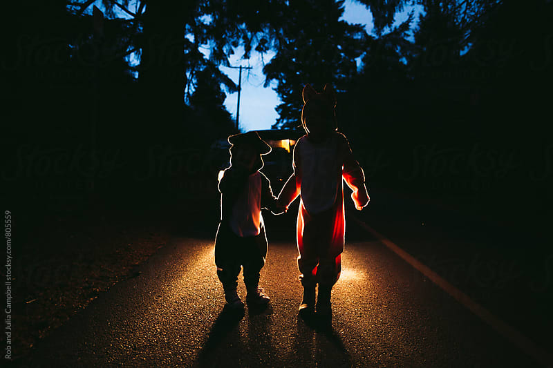 Children in fox and raccoon costumes standing in front of car headlights by Rob and Julia Campbell for Stocksy United