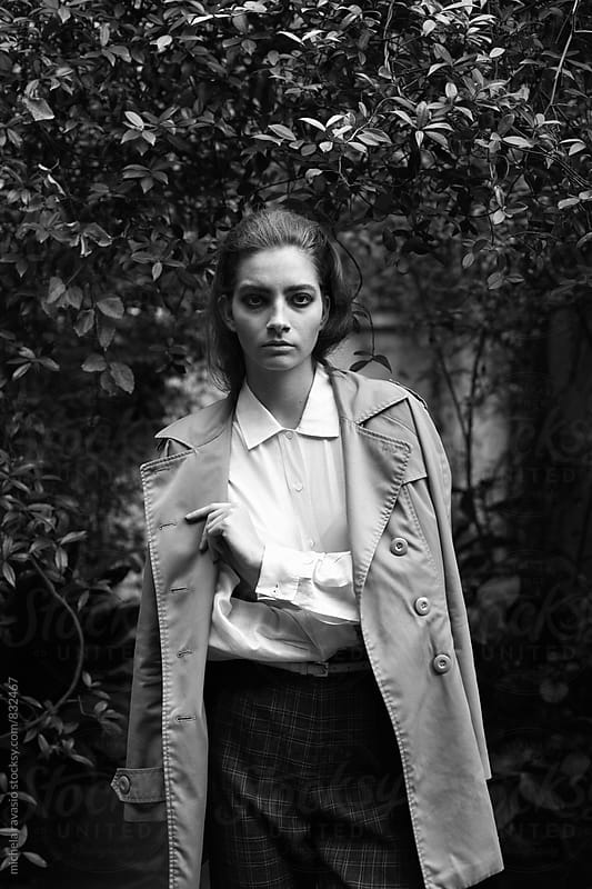 Attractive woman in trench coat looking at camera by michela ravasio for Stocksy United