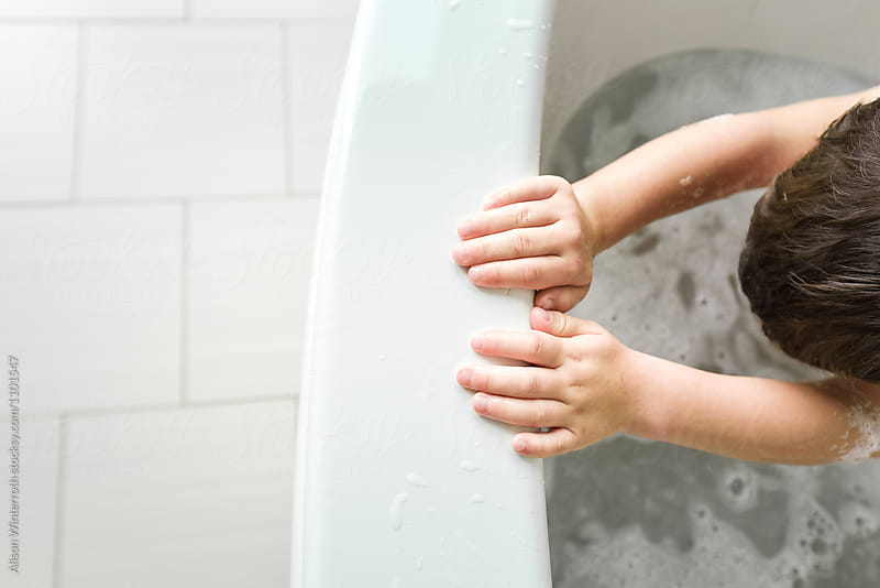 A Boy's Hand In A Bath Tub With Bubbles by Alison Winterroth for Stocksy United