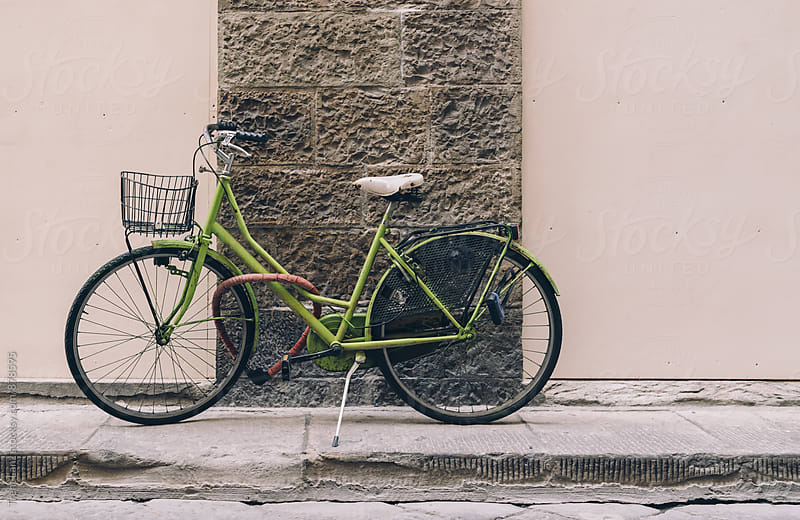 Green bicycle with basket parked on the sidewalk by Trent Lanz for Stocksy United