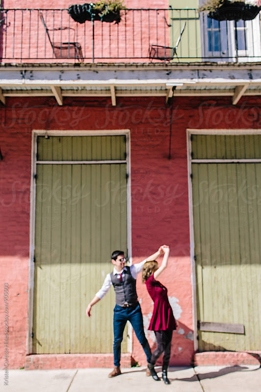 A blurry photo of a man twirling / dancing with a woman in the french quarter, New Orleans by Kristen Curette Hines for Stocksy United