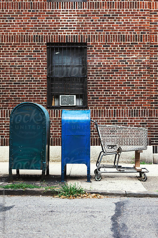Abandoned shopping cart next to the mailboxes. by BONNINSTUDIO for Stocksy United