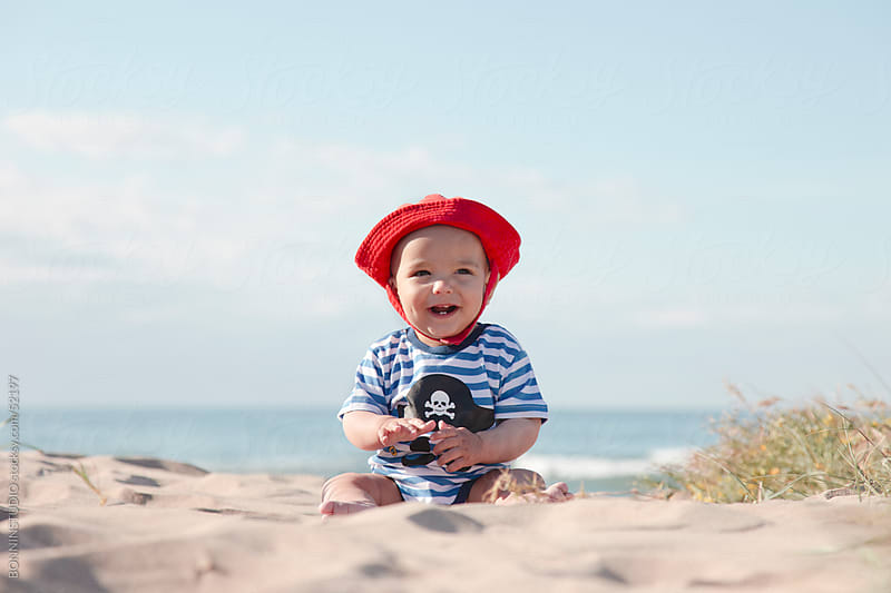 Baby sitting on the sand of the beach. Beautiful landscape. by BONNINSTUDIO for Stocksy United