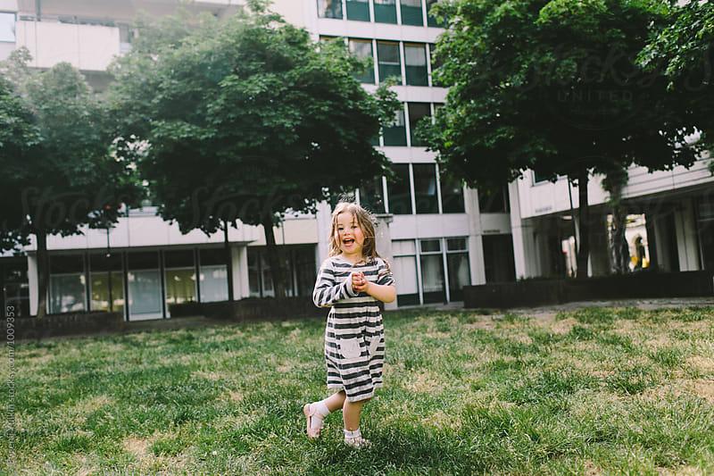Little girl in the town square by Evgenij Yulkin for Stocksy United