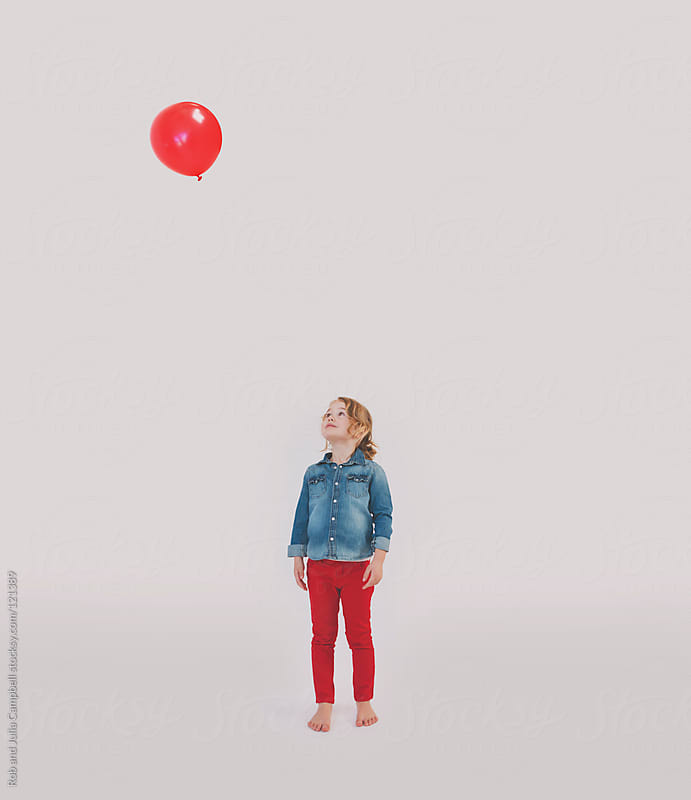 Stylish 4 year old girl staring up at red balloon on white backdrop by Rob and Julia Campbell for Stocksy United