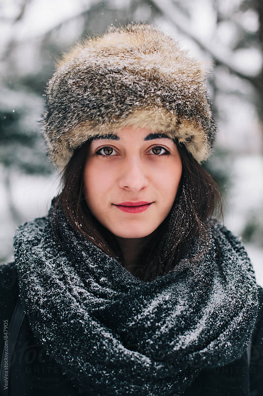 Portrait of a beautiful brunette woman wearing a fur hat outdoors by Marija Mandic for Stocksy United