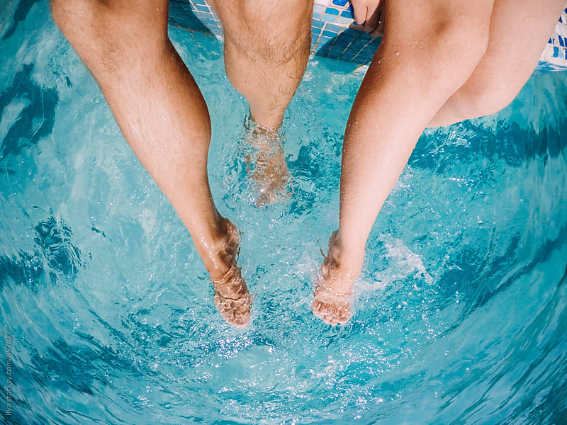 Young couple legs in pool water by Ilya for Stocksy United