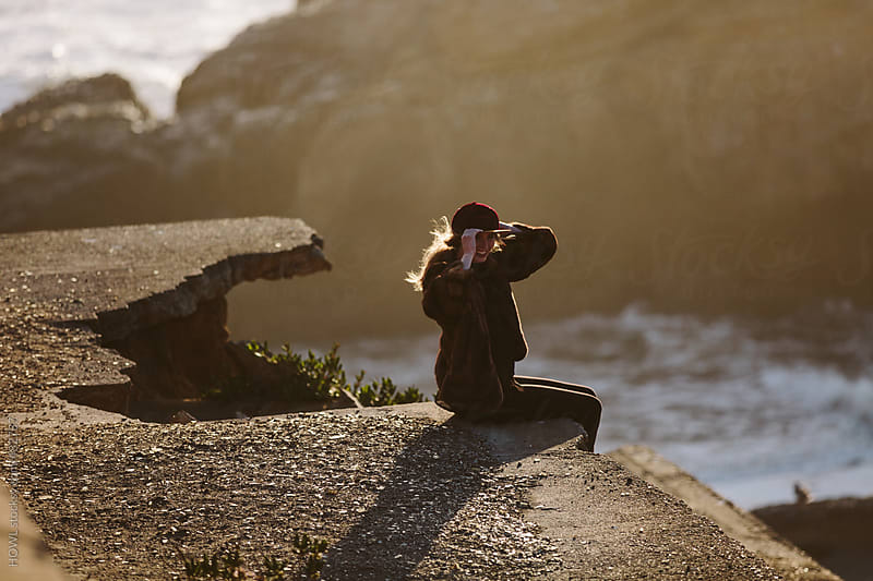 Young woman sitting alone at a vista on the California coast at sunset in San Francisco  by HOWL for Stocksy United