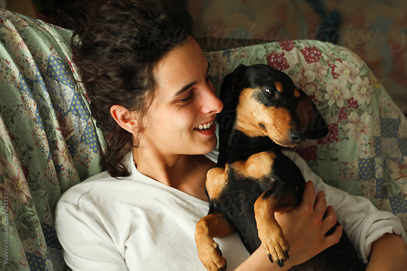 Young woman and her small black dog lying on the couch by Marija Mandic for Stocksy United