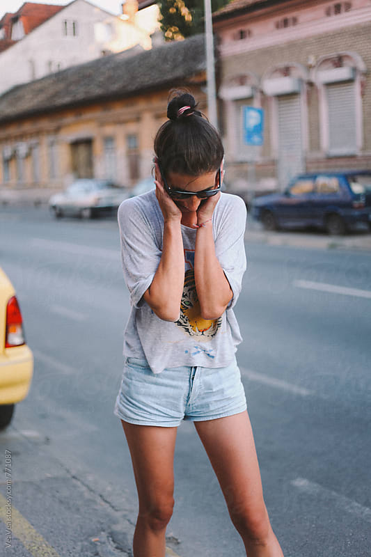 Attractive woman laughing in the street  by Marija Mandic for Stocksy United