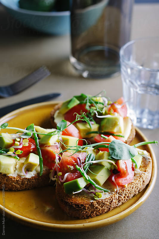Avocado,tomato and samphire toasts on a plate.Healthy avocado brunch. by Darren Muir for Stocksy United