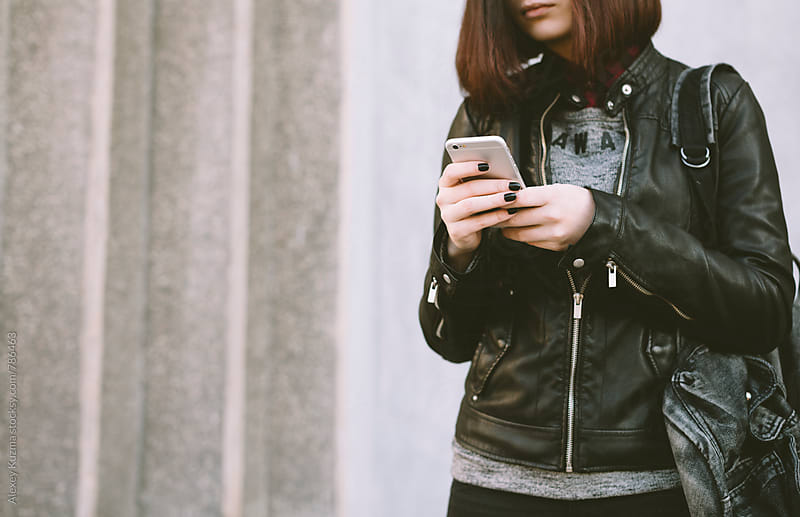 young woman using  phone on the street by Alexey Kuzma for Stocksy United