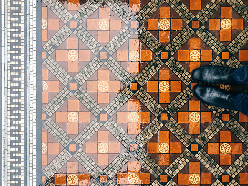 Standing on some pretty tiles in the rain in London by Kirstin Mckee for Stocksy United
