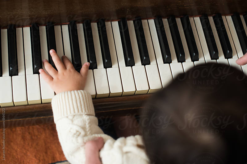 Toddler playing piano by Lauren Naefe for Stocksy United