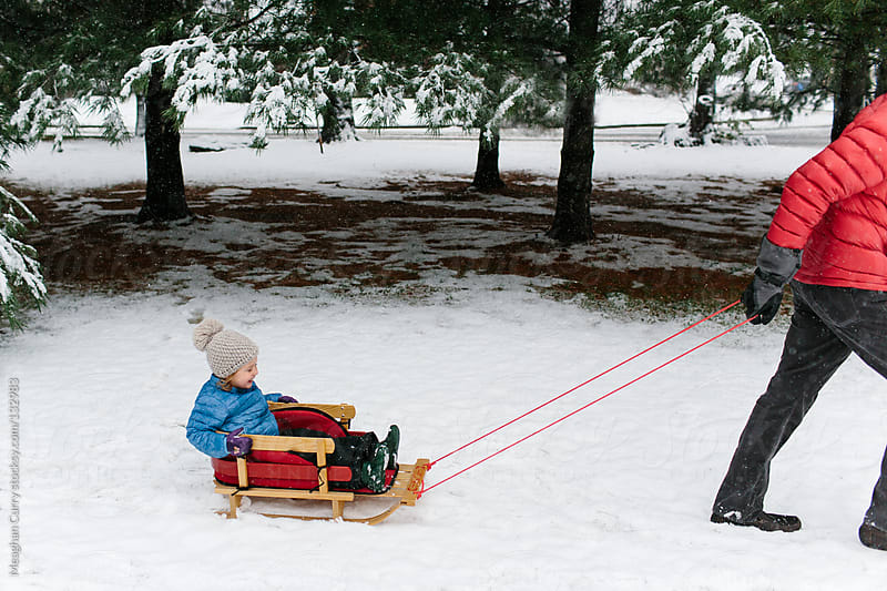 little girl being pulled on a sled through the snow by her father by Meaghan Curry for Stocksy United