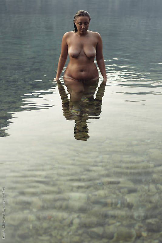 Portrait of naked woman standing in sea  by Katarina Simovic for Stocksy United