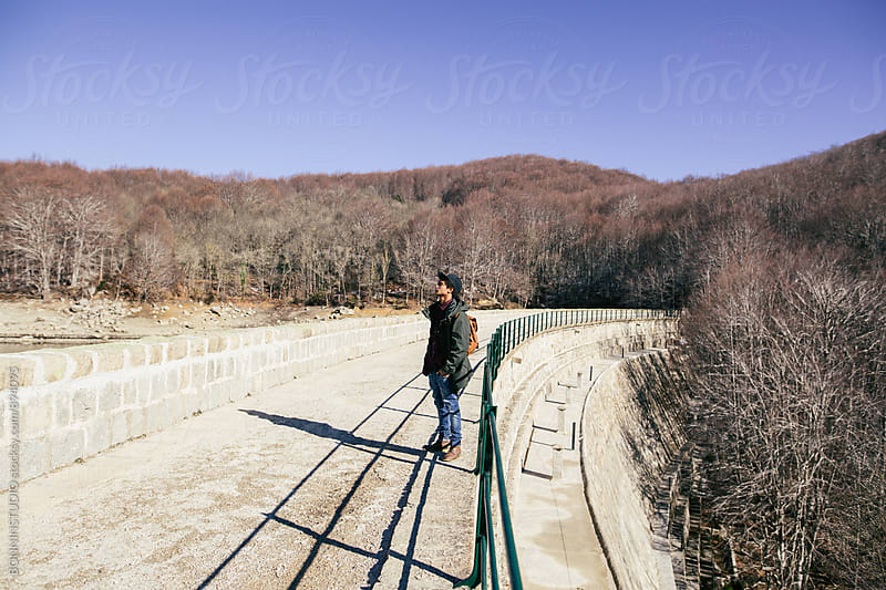 Side view of a mountaineer standing on bridge on a sunny winter day. by BONNINSTUDIO for Stocksy United