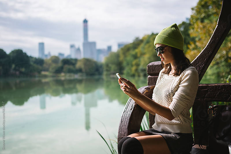 Young woman using a phone in Central Park, NYC by GIC for Stocksy United