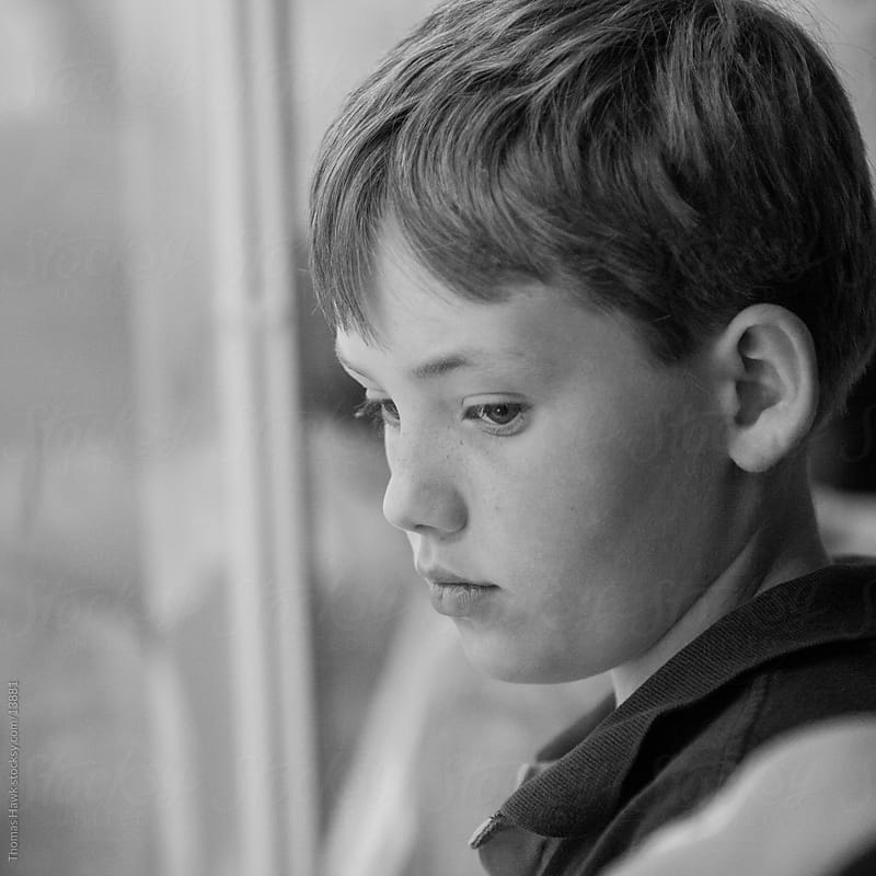 Boy looking through window by Thomas Hawk for Stocksy United