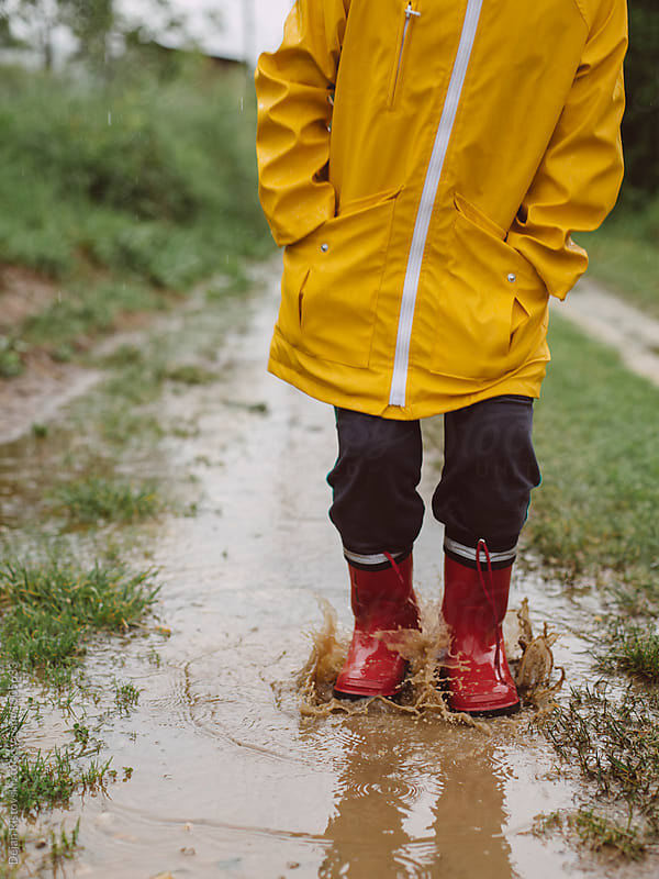 Child standing in puddle.  by Dejan Ristovski for Stocksy United