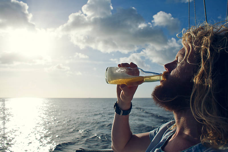 Bearded man on a boat drinking beer out of a bottle  by Denni Van Huis for Stocksy United