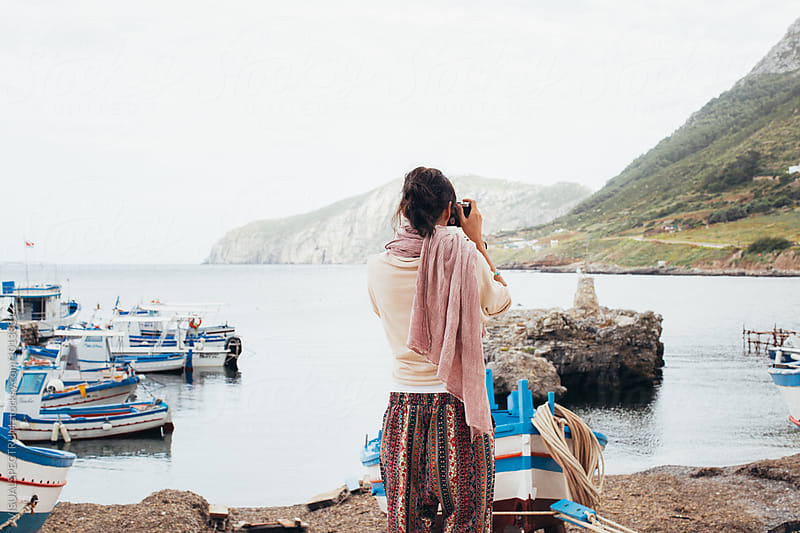 Woman Standing Alone in Small Mediterranean Port and Taking Photograph With Analog Camera by Julien L. Balmer for Stocksy United