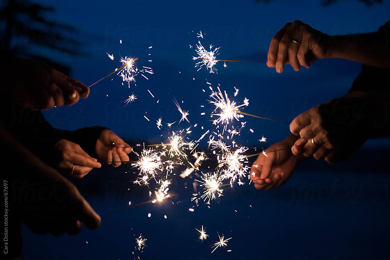 Hands hold lit sparklers at night by Cara Slifka for Stocksy United