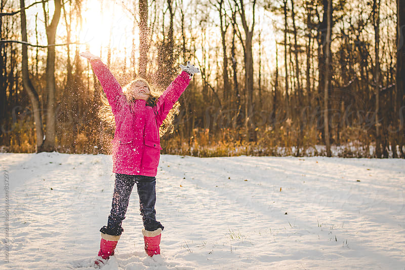 Girl throwing snow in the sunset by Lindsay Crandall for Stocksy United