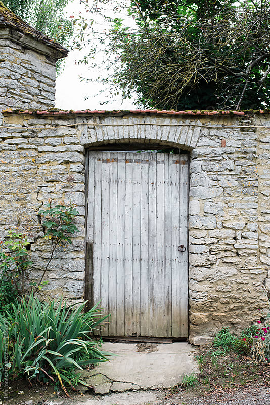 old door in stone wall by Léa Jones for Stocksy United