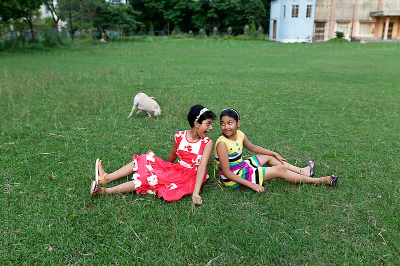 Teenage girl s sitting on green ground and making fun by PARTHA PAL for Stocksy United