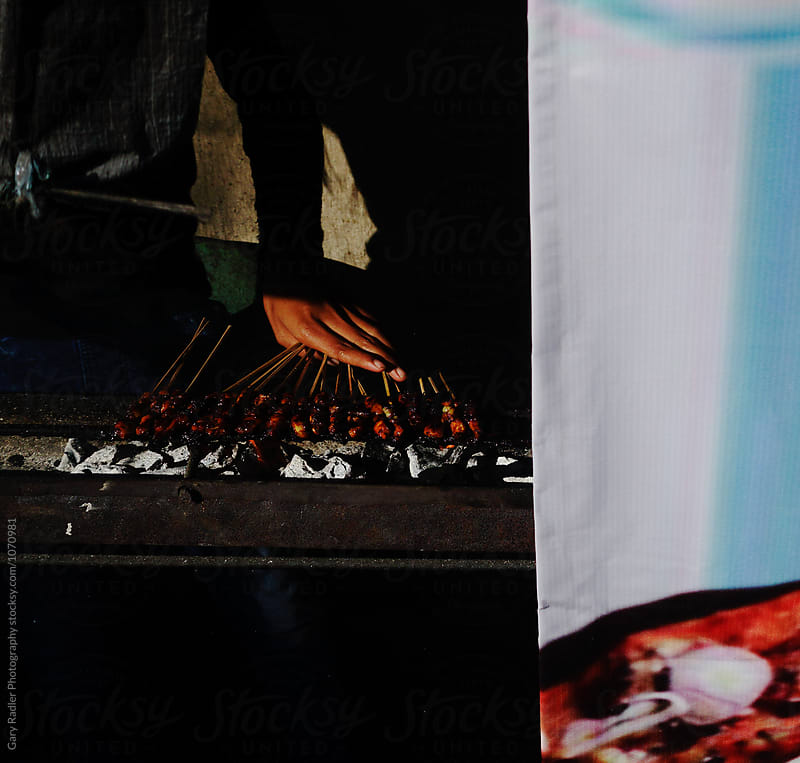 Hand of a Street Vendor cooking Sate in Bali by Gary Radler Photography for Stocksy United