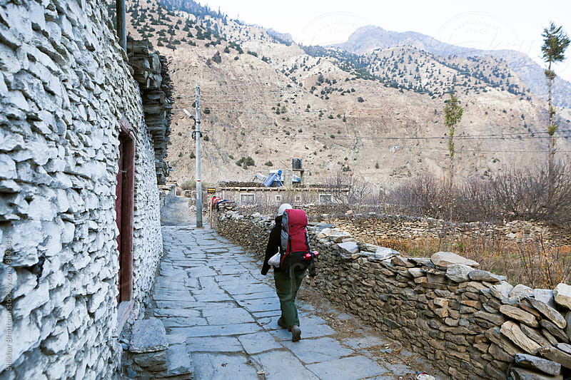A young traveller walking through a small village on her trek to the himalayas. by Shikhar Bhattarai for Stocksy United