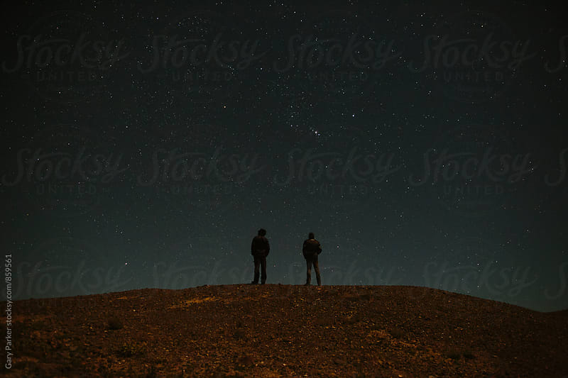 Two people stand on a hill staring at the stars by Gary Parker for Stocksy United