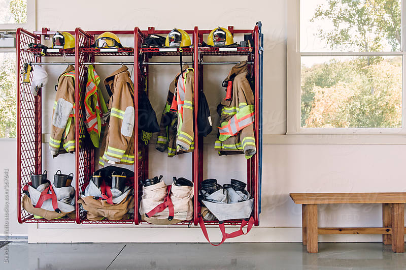 firefighters' uniforms inside a firehouse by Deirdre Malfatto for Stocksy United