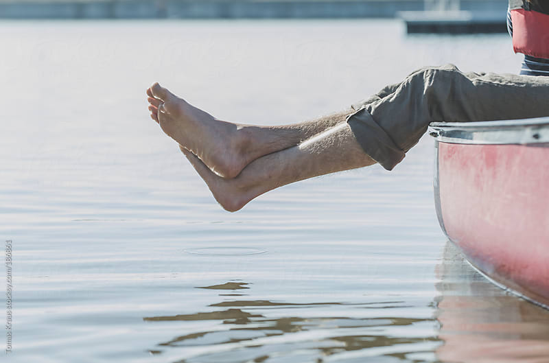 A Man's Feet Over the Side of a Canoe by Tomas Kraus for Stocksy United
