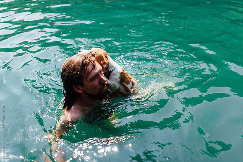 Man swimming with dog by Boris Jovanovic for Stocksy United