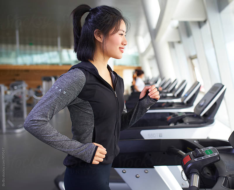 young asian woman running in gym by cuiyan Liu for Stocksy United