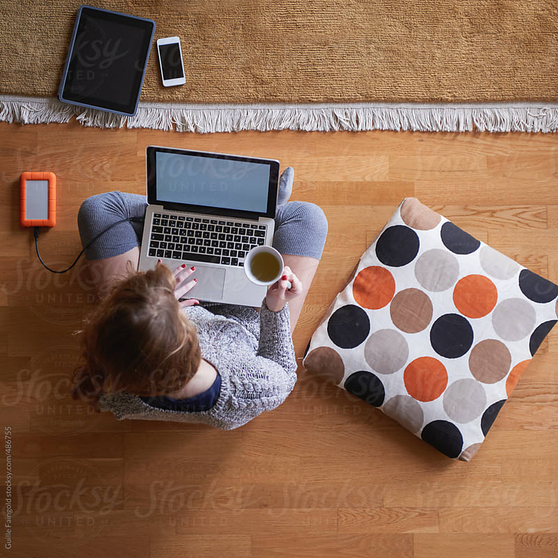 From above: young woman using her laptop at home by Guille Faingold for Stocksy United