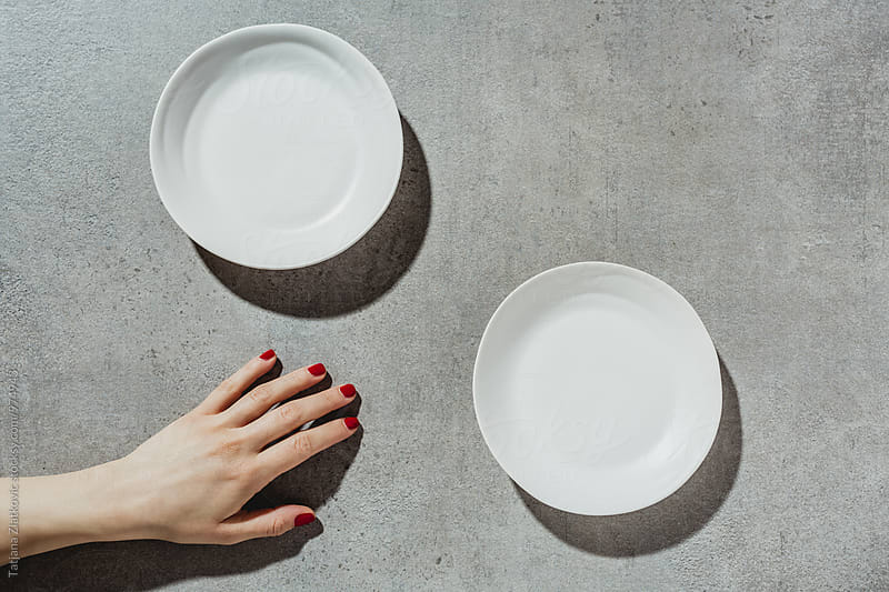 Hand and plates by Tatjana Zlatkovic for Stocksy United