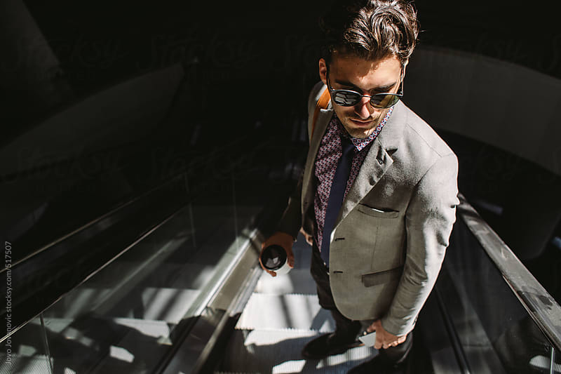 Stylish young man on an escalator by Jovo Jovanovic for Stocksy United