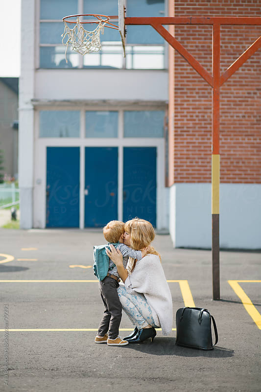 Mother embracing her son at a school playground by Ania Boniecka for Stocksy United