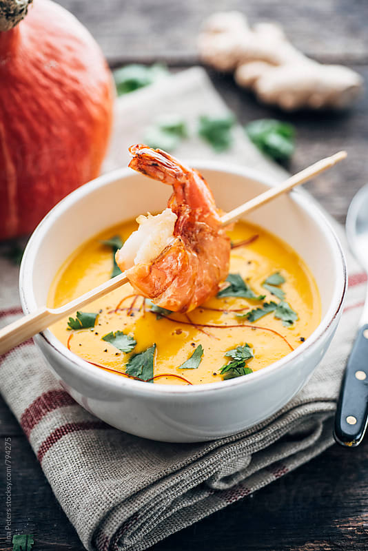 Food: Squash soup with fried prawn, cilantro and chili strings by Ina Peters for Stocksy United