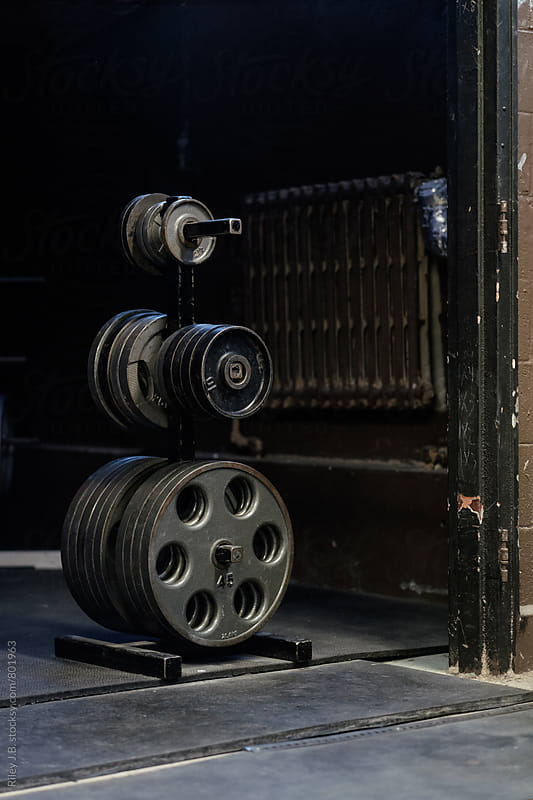 Weight plates on a rack in an old, gritty gym. by Riley J.B. for Stocksy United