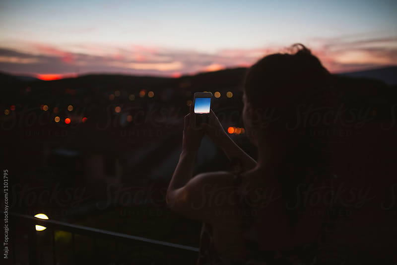 Silhouette of a woman at night taking photos by Maja Topcagic for Stocksy United