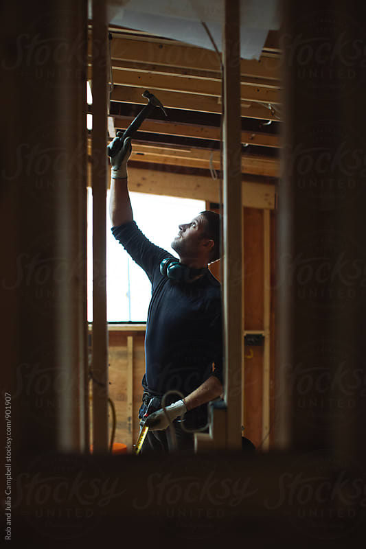 Man working with hammer on construction jobsite by Rob and Julia Campbell for Stocksy United