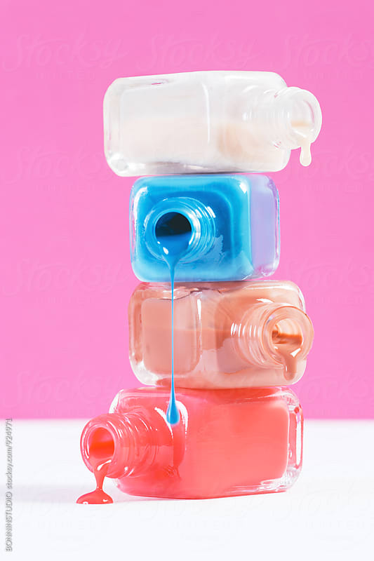 Stack of opened nail polish bottles on colorful background. by BONNINSTUDIO for Stocksy United