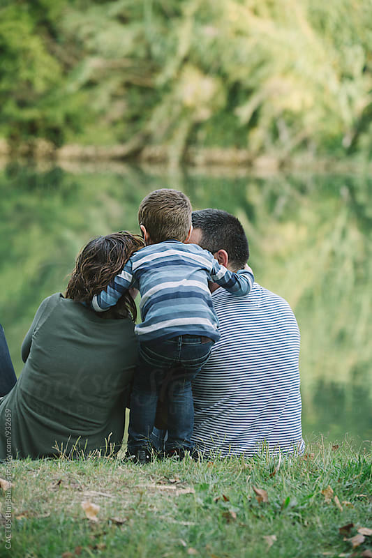 Tender family moment by the river by CACTUS Blai Baules for Stocksy United