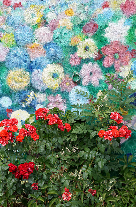 red roses in front of a flower mural by Marcel for Stocksy United