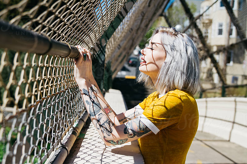 portrait of urban young female in city next to chain link fence by Jesse Morrow for Stocksy United