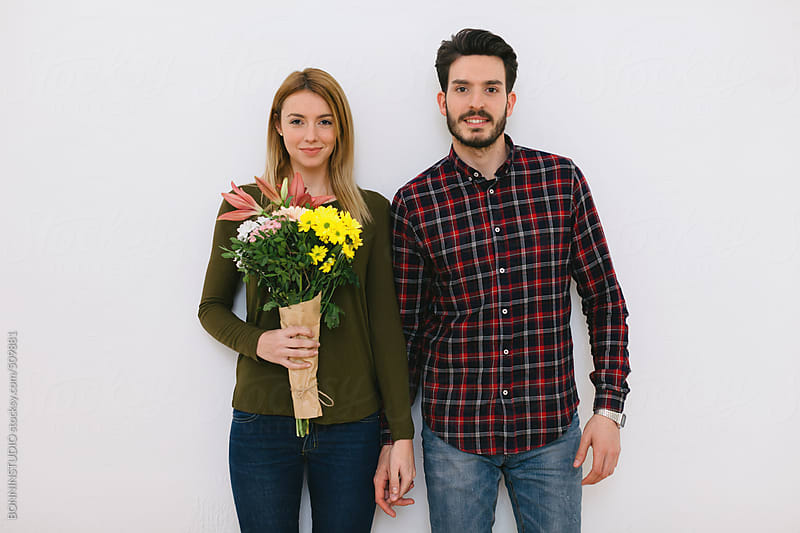 Young couple in love holding a bouquet of flowers on Valentine's day.  by BONNINSTUDIO for Stocksy United